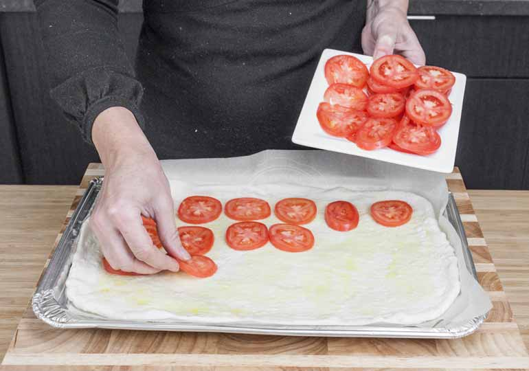 Place tomatoes on dough